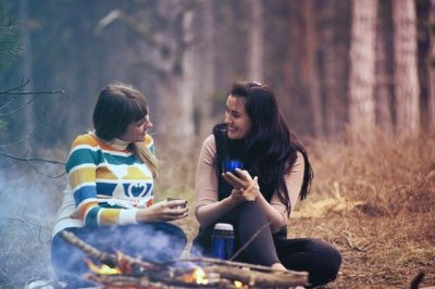 two women sitting by campfire talking